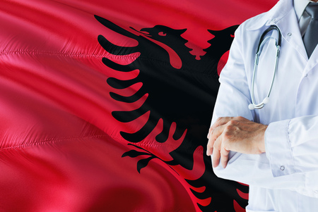 Albanian Doctor standing with stethoscope on Albania flag background. National healthcare system concept, medical theme.