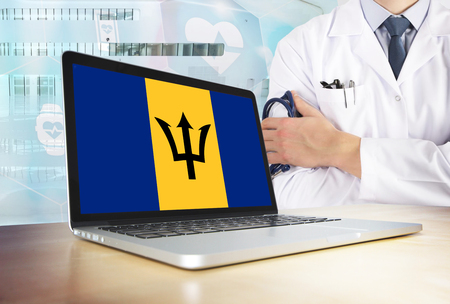 Barbados healthcare system in tech theme. Barbadian flag on computer screen. Doctor standing with stethoscope in hospital. Cryptocurrency and Blockchain concept.