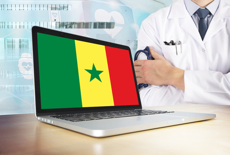 Senegal healthcare system in tech theme. Senegalese flag on computer screen. Doctor standing with stethoscope in hospital. Cryptocurrency and Blockchain concept.