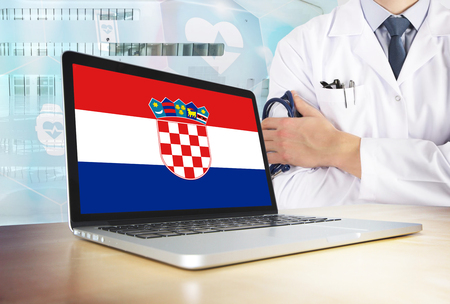 Croatia healthcare system in tech theme. Croatian flag on computer screen. Doctor standing with stethoscope in hospital. Cryptocurrency and Blockchain concept. 版權商用圖片