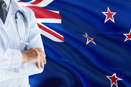 Kiwi Doctor standing with stethoscope on New Zealand flag background. National healthcare system concept, medical theme.