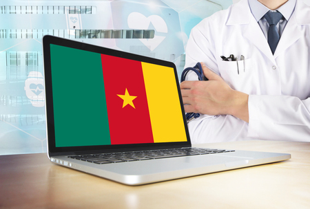 Cameroon healthcare system in tech theme. Cameroonian flag on computer screen. Doctor standing with stethoscope in hospital. Cryptocurrency and Blockchain concept. Banco de Imagens