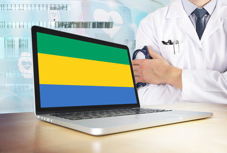 Gabon healthcare system in tech theme. Gabonese flag on computer screen. Doctor standing with stethoscope in hospital. Cryptocurrency and Blockchain concept.