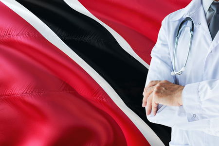 Doctor standing with stethoscope on Trinidad And Tobago flag background. National healthcare system concept, medical theme.