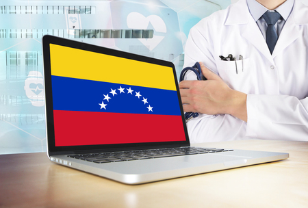 Venezuela healthcare system in tech theme. Venezuelan flag on computer screen. Doctor standing with stethoscope in hospital. Cryptocurrency and Blockchain concept.