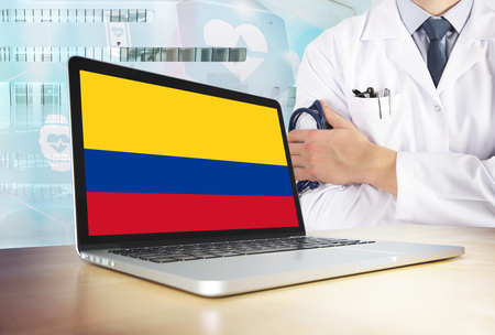 Colombia healthcare system in tech theme. Colombian flag on computer screen. Doctor standing with stethoscope in hospital. Cryptocurrency and Blockchain concept. Reklamní fotografie