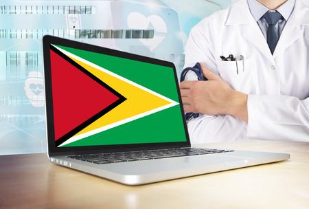 Guyana healthcare system in tech theme. Guyanese flag on computer screen. Doctor standing with stethoscope in hospital. Cryptocurrency and Blockchain concept.