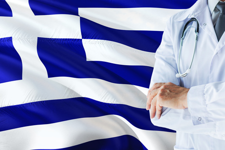 Greek Doctor standing with stethoscope on Greece flag background. National healthcare system concept, medical theme.