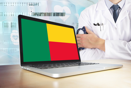 Benin healthcare system in tech theme. Beninese flag on computer screen. Doctor standing with stethoscope in hospital. Cryptocurrency and Blockchain concept. 스톡 콘텐츠