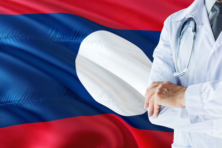 Doctor standing with stethoscope on Laos flag background. National healthcare system concept, medical theme.