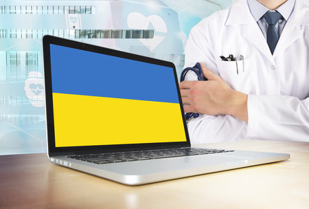 Ukraine healthcare system in tech theme. Ukrainian flag on computer screen. Doctor standing with stethoscope in hospital. Cryptocurrency and Blockchain concept.