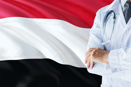 Yemeni Doctor standing with stethoscope on Yemen flag background. National healthcare system concept, medical theme.