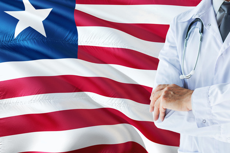 Liberian Doctor standing with stethoscope on Liberia flag background. National healthcare system concept, medical theme.