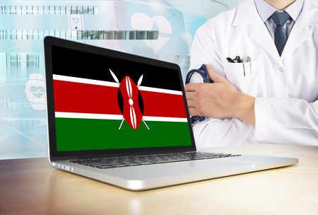 Kenya healthcare system in tech theme. Kenyan flag on computer screen. Doctor standing with stethoscope in hospital. Cryptocurrency and Blockchain concept.