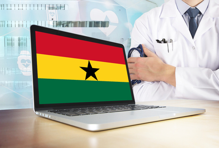 Ghana healthcare system in tech theme. Ghanaian flag on computer screen. Doctor standing with stethoscope in hospital. Cryptocurrency and Blockchain concept. Banco de Imagens