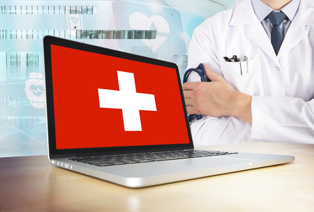 Switzerland healthcare system in tech theme. Swiss flag on computer screen. Doctor standing with stethoscope in hospital. Cryptocurrency and Blockchain concept.