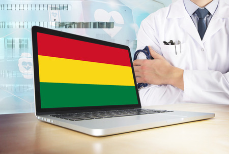 Bolivia healthcare system in tech theme. Bolivian flag on computer screen. Doctor standing with stethoscope in hospital. Cryptocurrency and Blockchain concept. Banco de Imagens