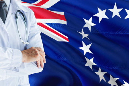 Doctor standing with stethoscope on Cook Islands flag background. National healthcare system concept, medical theme.