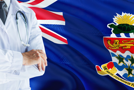 Doctor standing with stethoscope on Cayman Islands flag background. National healthcare system concept, medical theme.