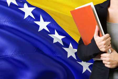 Learning Bosnian language concept. Young woman standing with the Bosnia Herzegovina flag in the background. Teacher holding books, orange blank book cover. 版權商用圖片