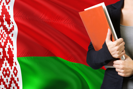 Learning Belarusian language concept. Young woman standing with the Belarus flag in the background. Teacher holding books, orange blank book cover.