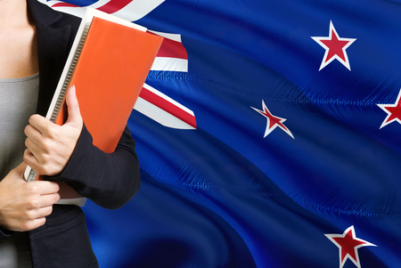Learning language concept. Young woman standing with the New Zealand flag in the background. Teacher holding books, orange blank book cover.