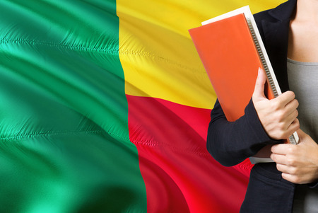 Learning Beninese language concept. Young woman standing with the Benin flag in the background. Teacher holding books, orange blank book cover. 版權商用圖片