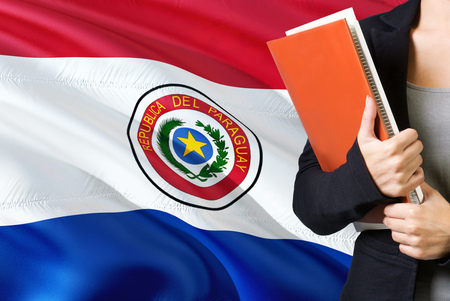 Learning Paraguayan language concept. Young woman standing with the Paraguay flag in the background. Teacher holding books, orange blank book cover.