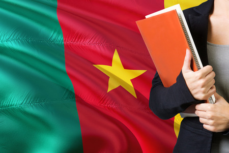 Learning Cameroonian language concept. Young woman standing with the Cameroon flag in the background. Teacher holding books, orange blank book cover.