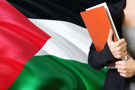 Learning Palestinian language concept. Young woman standing with the Palestine flag in the background. Teacher holding books, orange blank book cover. 版權商用圖片