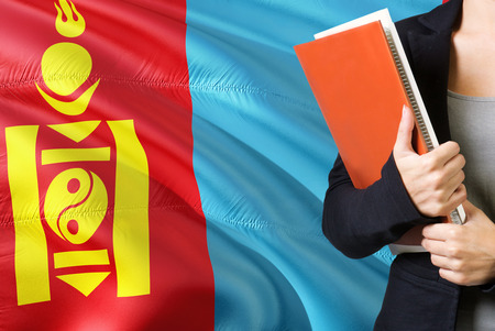 Learning Mongolian language concept. Young woman standing with the Mongolia flag in the background. Teacher holding books, orange blank book cover.