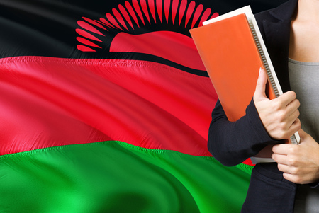Learning Malawian language concept. Young woman standing with the Malawi flag in the background. Teacher holding books, orange blank book cover.