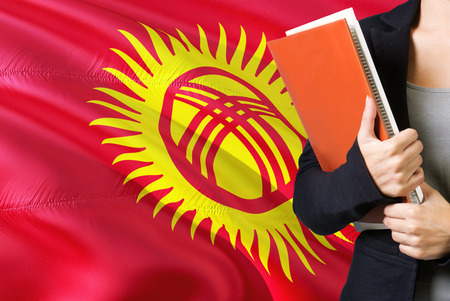Learning Kyrgyz language concept. Young woman standing with the Kyrgyzstan flag in the background. Teacher holding books, orange blank book cover.