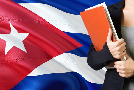 Learning Cuban language concept. Young woman standing with the Cuba flag in the background. Teacher holding books, orange blank book cover. Stok Fotoğraf