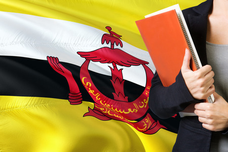 Learning Bruneian language concept. Young woman standing with the Brunei flag in the background. Teacher holding books, orange blank book cover. Фото со стока