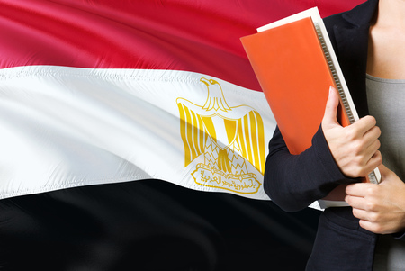 Learning Egyptian language concept. Young woman standing with the Egypt flag in the background. Teacher holding books, orange blank book cover. Фото со стока