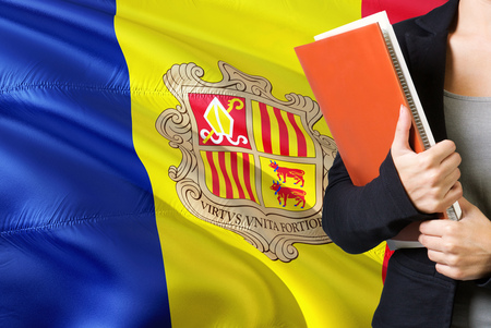 Learning Andorran language concept. Young woman standing with the Andorra flag in the background. Teacher holding books, orange blank book cover.