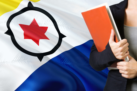 Learning language concept. Young woman standing with the Bonaire flag in the background. Teacher holding books, orange blank book cover.