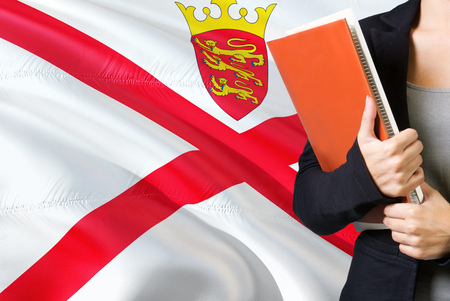 Learning language concept. Young woman standing with the Jersey flag in the background. Teacher holding books, orange blank book cover.