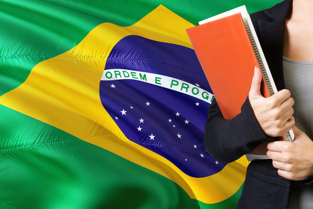 Learning Brazilian language concept. Young woman standing with the Brazil flag in the background. Teacher holding books, orange blank book cover.