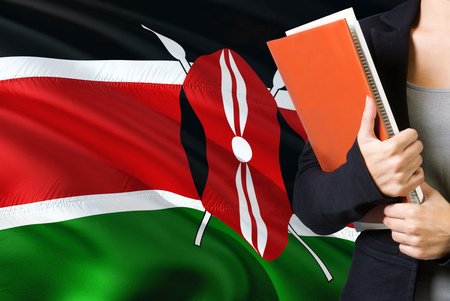 Learning Kenyan language concept. Young woman standing with the Kenya flag in the background. Teacher holding books, orange blank book cover.