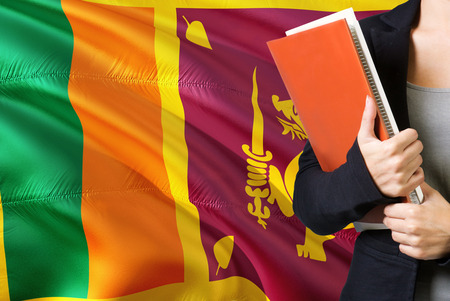 Learning Sri Lankan language concept. Young woman standing with the Sri Lanka flag in the background. Teacher holding books, orange blank book cover. Stok Fotoğraf