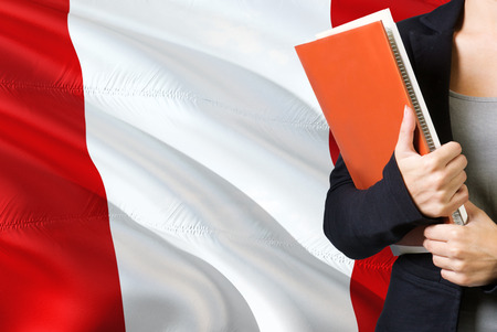 Learning Peruvian language concept. Young woman standing with the Peru flag in the background. Teacher holding books, orange blank book cover.