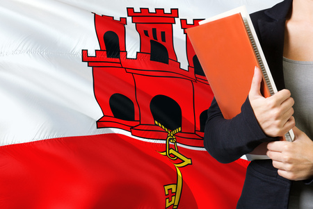 Learning language concept. Young woman standing with the Gibraltar flag in the background. Teacher holding books, orange blank book cover.