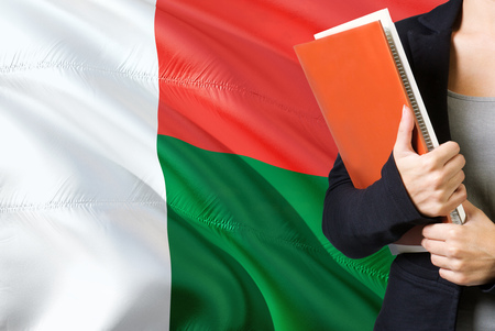 Learning Malagasy language concept. Young woman standing with the Madagascar flag in the background. Teacher holding books, orange blank book cover.