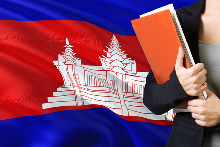 Learning Cambodian language concept. Young woman standing with the Cambodia flag in the background. Teacher holding books, orange blank book cover.
