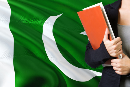Learning Pakistani language concept. Young woman standing with the Pakistan flag in the background. Teacher holding books, orange blank book cover.