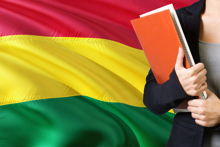 Learning Bolivian language concept. Young woman standing with the Bolivia flag in the background. Teacher holding books, orange blank book cover. Stock Photo