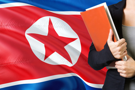 Learning North Korean language concept. Young woman standing with the North Korea flag in the background. Teacher holding books, orange blank book cover. Фото со стока