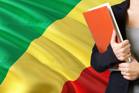 Learning Congolese language concept. Young woman standing with the Republic Of The Congo flag in the background. Teacher holding books, orange blank book cover.